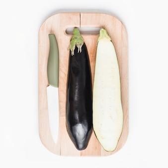 Messer und Aubergine auf Schneidebrett