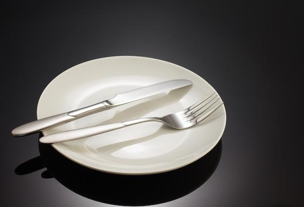 Messer und gabel am teller auf schwarzem hintergrund