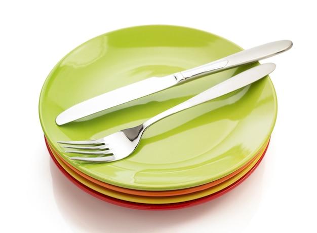 Messer und gabel an platte lokalisiert auf weißem hintergrund