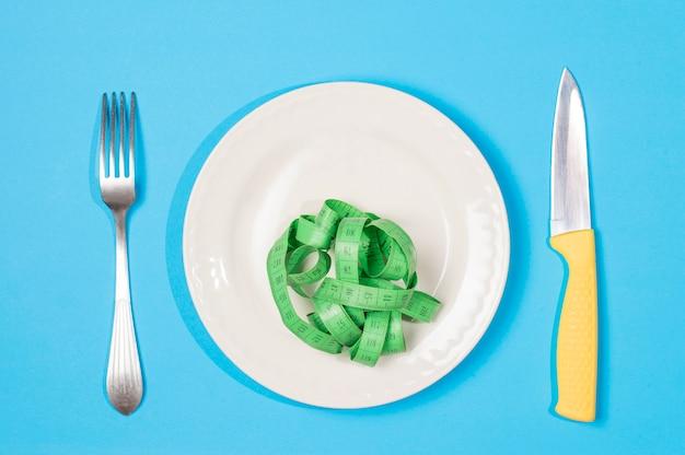 Messer und gabel nahe auf einer platte, auf der messinstrumentplatte, das konzept des verlierens des gewichts