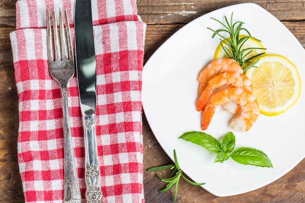 Messer und gabel neben einem teller mit gekochten garnelen