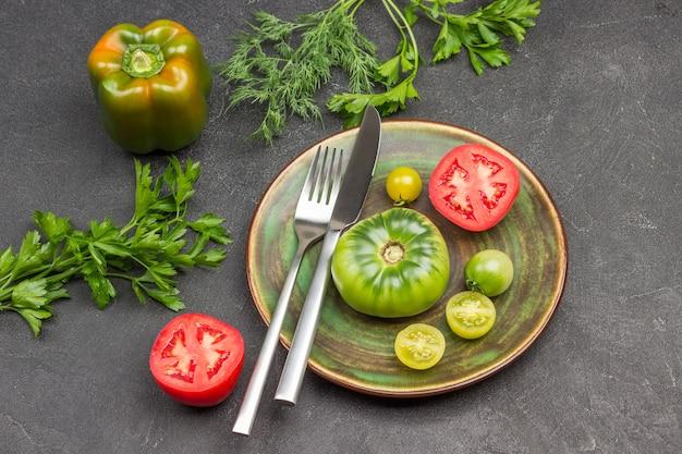 Messer und gabel, rote und grüne tomate auf teller. pfeffer und petersilie auf dem tisch. schwarzer hintergrund. ansicht von oben