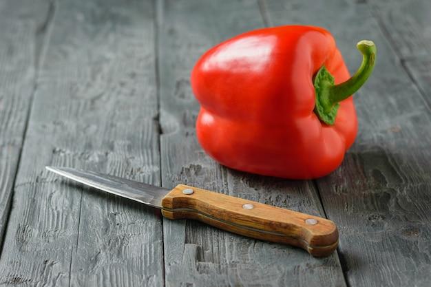 Messer und reifer roter pfeffer liegen auf der seite auf einem holztisch. vegetarisches essen. konzept der gesunden ernährung.