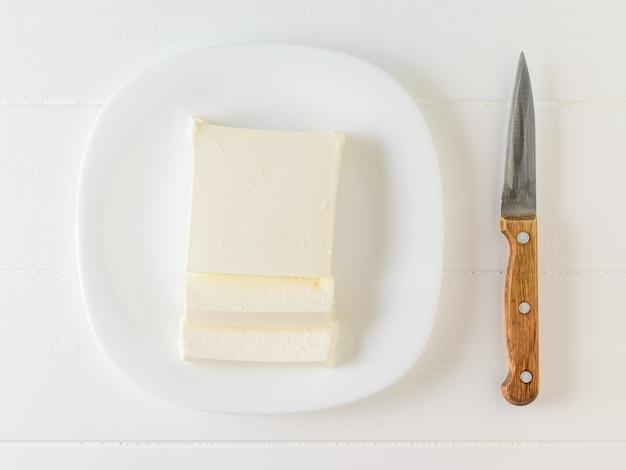 Messer und serbischer käse auf einer weißen schüssel auf einem weißen tisch