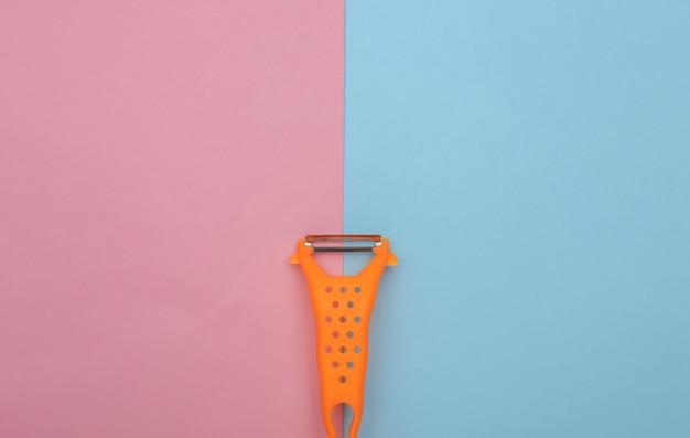Messer zum schälen der haut auf blauem rosa hintergrund. ansicht von oben