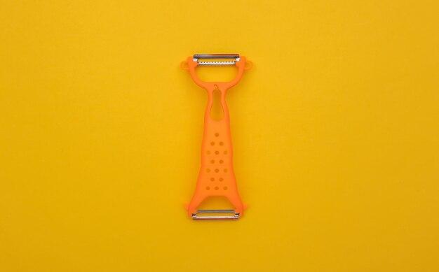 Messer zum schälen der haut auf gelbem hintergrund. ansicht von oben