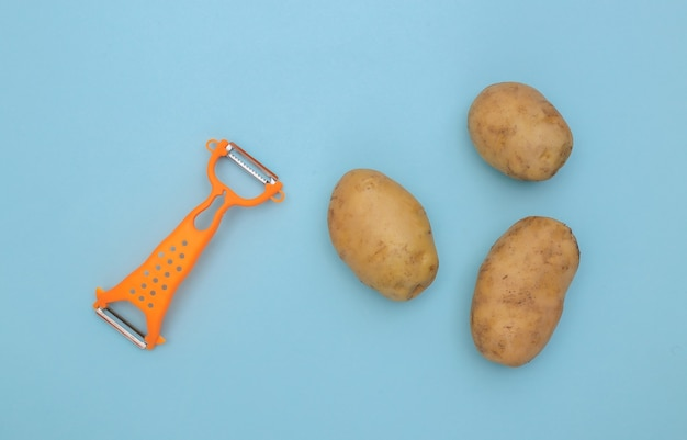Messer zum schälen von haut und kartoffeln auf blauem hintergrund. ansicht von oben
