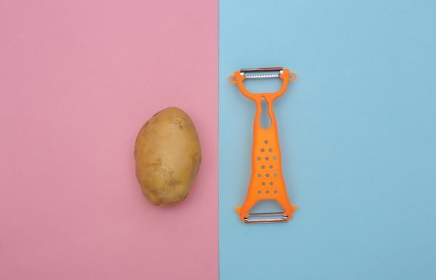 Messer zum schälen von haut und kartoffeln auf blauem pibk-hintergrund. ansicht von oben