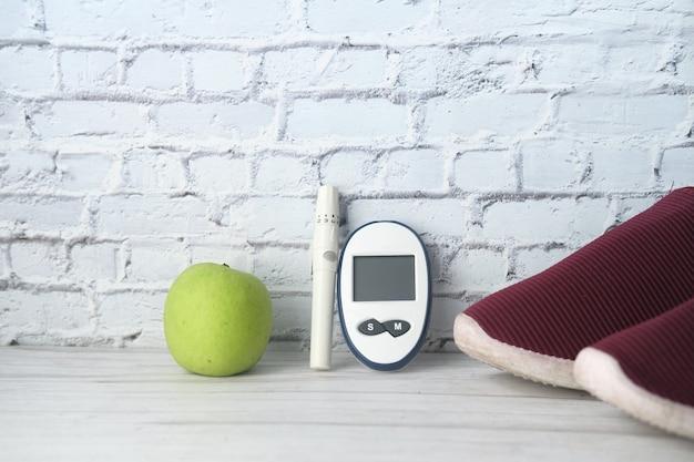Messgeräte für diabetiker, schuh und apfel auf dem tisch