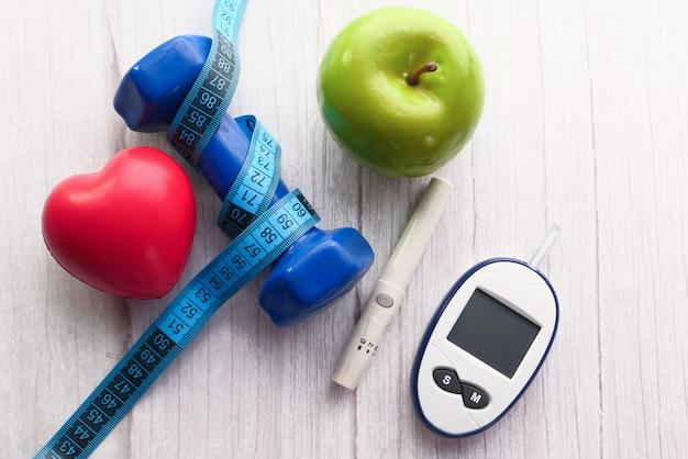 Messgeräte für diabetiker und hantel und apfel auf dem tisch