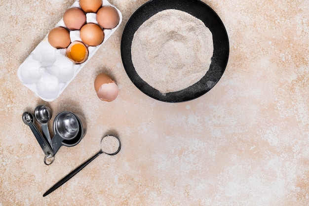 Messlöffel mit haferstall; mehl; eierkarton auf beige hintergrund