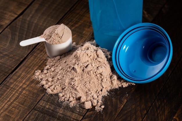 Messlöffel molkenprotein auf holztisch zur zubereitung eines milchshakes.