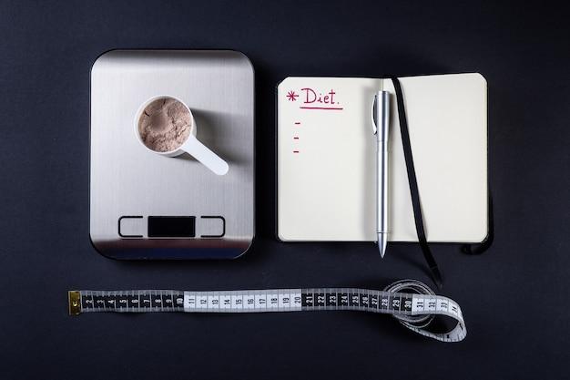 Messlöffel molkenprotein, notizbuch, waage und maßband für diät.