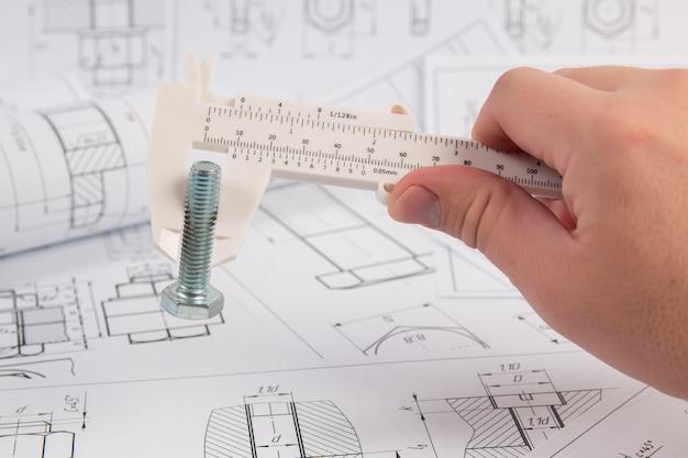Messung der schraubenabmessungen mit einem technischen messschieber. arbeit des ingenieurs.