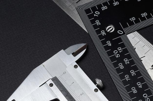Messwerkzeug, lineal und messschieber. auf dunklem hintergrund liegen. nahansicht.