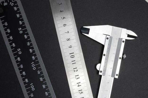 Messwerkzeug, lineal und messschieber. auf dunklem hintergrund liegen. nahaufnahme.
