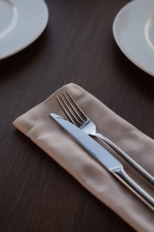 Metal messer und gabel auf einer hellen serviette auf einem holztisch