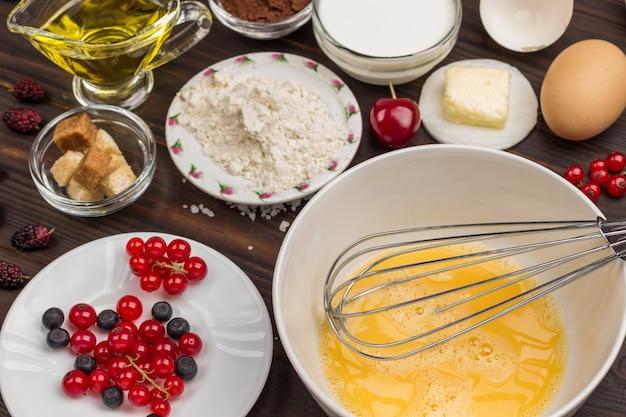 Metall schneebesen in weißer schüssel mit geschlagenen eiern. beeren, mehl, butter auf dem tisch. dunkle holzoberfläche. draufsicht. nahansicht
