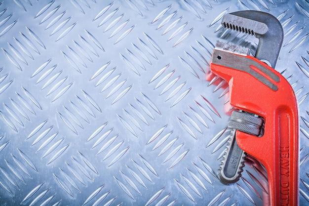 Metall-schraubenschlüssel auf geriffeltem metallplatten-kopierraum-konstruktionskonzept