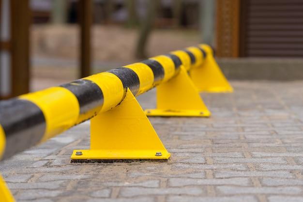 Metall-sicherheitszaun mit gelbem und schwarzem streifen auf dem parkplatz.