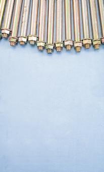 Metallankerbolzen für betonwände und muttern auf metallischem hintergrund kopieren raumbildkonstruktionskonzept