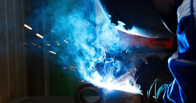 Metallarbeiter, der mit fackel in der metallindustriefabrik schweißt