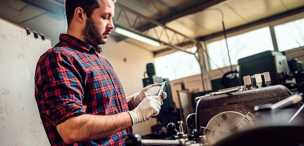 Metallarbeiter turner, der schieber durch die drehbankmaschine verwendet