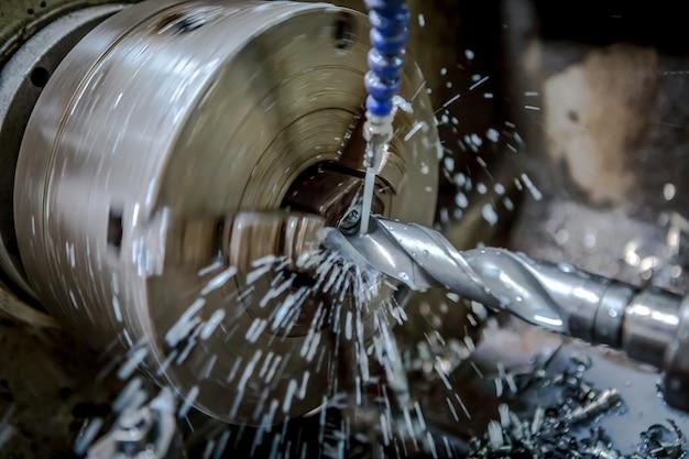 Metallbearbeitung-drehmaschine bohrt ein werkstück mit ausgebreitetem kühlwasser
