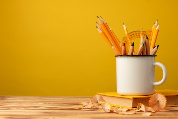 Metallbecher mit scharfen stiften und bleistiftschnitzeln auf hölzernem schreibtisch gegen gelben hintergrund
