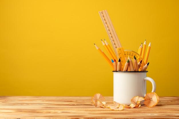 Metallbecher mit scharfen stiften und bleistiftschnitzeln auf holzschreibtisch auf gelb