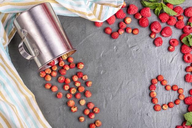 Metallbecher mit walderdbeeren auf schwarzem