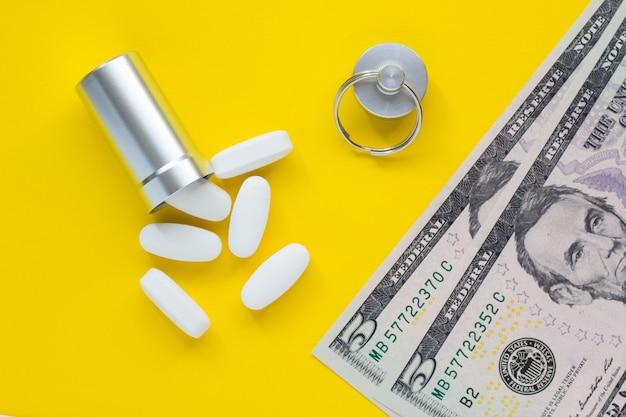 Metallbehälter für pillen und geld auf gelbem hintergrund, konzept der teuren drogen, nahaufnahme
