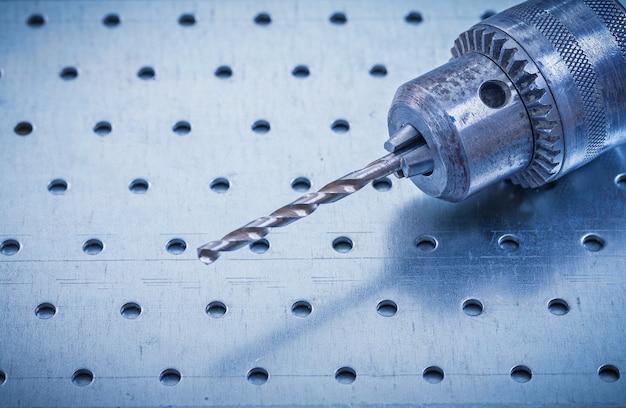 Metallbohrer auf perforiertem metallischem hintergrundkonstruktionskonzept