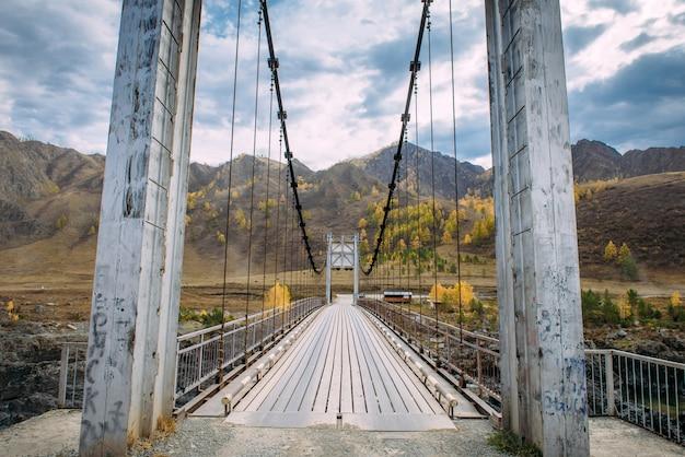 Metallbrücke über fluss auf bergen und sturmwolkenhintergrund. kombinierte fußgänger- und straßenbrücke über den fluss im hochland. auto reisen um die welt.