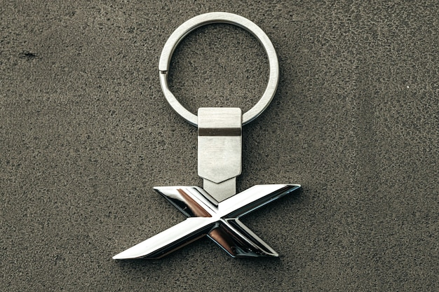Metallbuchstabe x autoschlüssel auf dunklem betonhintergrund