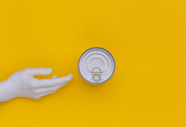 Metalldose konserven und mannequin hand auf gelbem hintergrund. minimalismus. ansicht von oben