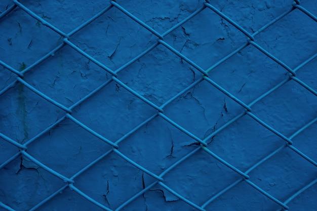 Metalldrahtgitter auf dem hintergrund einer alten blauen wand mit abblätternder farbe. maschentextur als konzept von begrenzung, unfreiheit oder schutz und sicherheit