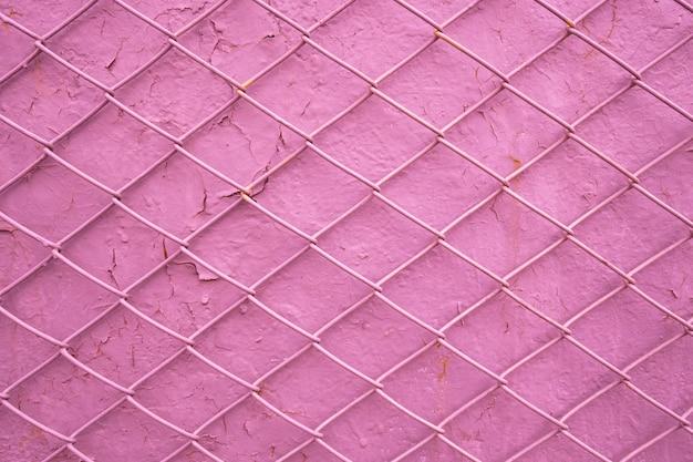 Metalldrahtgitter auf dem hintergrund einer alten rosa wand mit abblätternder farbe. maschentextur als konzept der einschränkung der männlichen freiheit, der abhängigkeit von frauen, des mangels an freiheit, der sucht