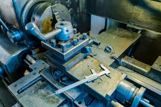 Metalldrehmaschine bearbeitet metallteile bei der produktion im werk.
