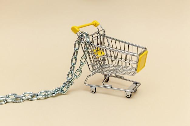 Metalleinkaufswagen mit metallkette auf beigem hintergrund konzeptobjekte für supermarkt