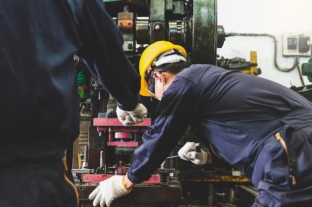 Metallfabrikingenieure mit schutzhelm, gesichtsmaske und handschuhen halten die tablet-computer an der technischen herstellung von metallteilen mit drehmaschinen in einer industrieanlage fest.