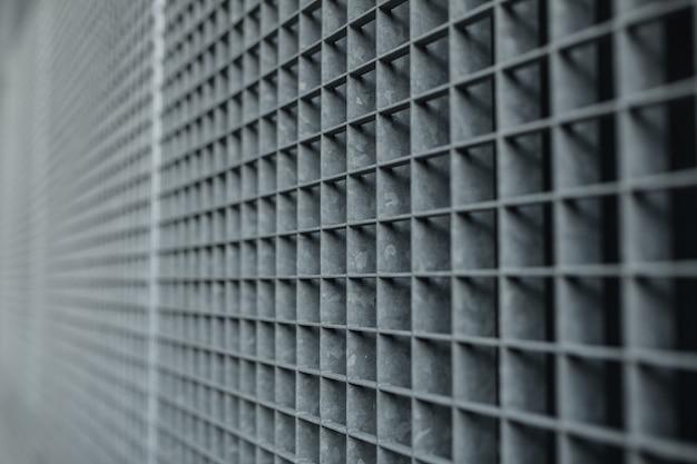 Metallgitter mit hintergrund des gitters der kleinen zellen auf lager mit flachem dof und selektivem fokus