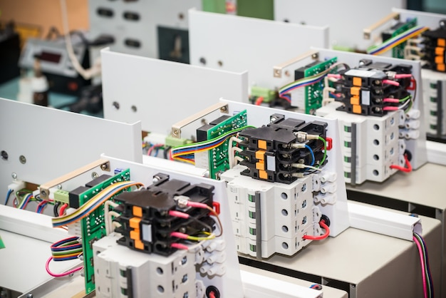 Metallgittergehäuse für netzteil und kabel stehen auf einem holztisch bei der herstellung von high-tech-computern. konzept der hochtechnologie und der industriellen produktion