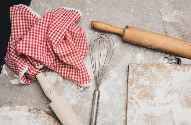 Metallhandmischer, hölzerne nudelhölzer und bestreutes mehl auf einem holzbrett, draufsicht