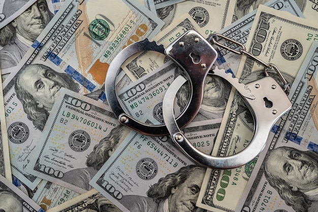 Metallhandschellen an hundert-dollar-banknoten
