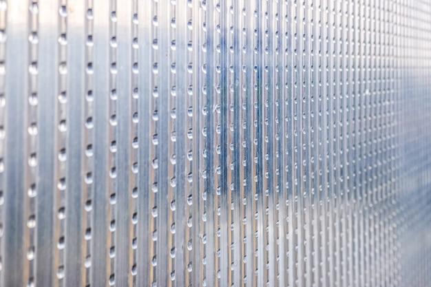 Metallische beschaffenheit einer aluminiumplatte mit schlitzen für gebrauch als industrieller hintergrund.