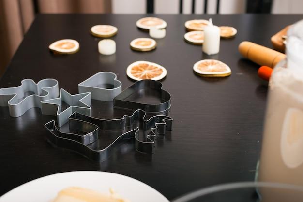 Metallische formen zum schneiden von lebkuchenplätzchen werden auf einem schwarzen tisch vorbereitet.