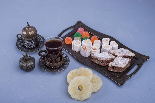 Metallische gebäckplatte mit köstlichkeiten und einem glas tee