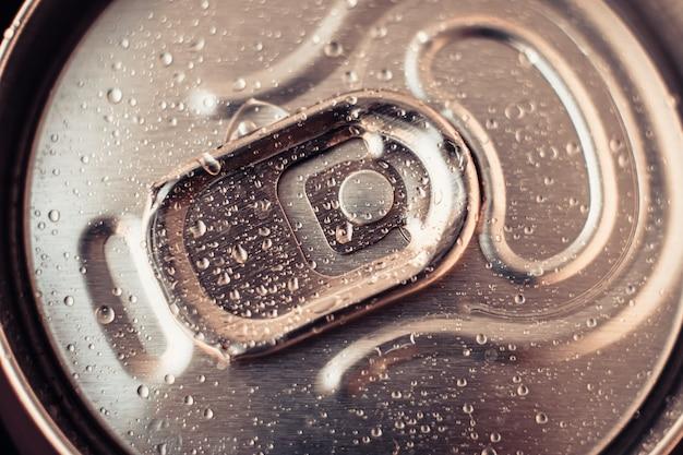 Metallische getränkedose mit wassertropfen. glänzendes bier kann nahaufnahme. goldene flasche getränk, deckel der cola-verpackung. draufsicht.