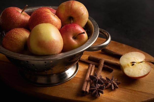 Metallische schale voller roter reifer äpfel, verstreuter zimtstangen, anis-sterne eine halbe apfel auf holz schneidebrett stillleben. apfelkuchen-zutaten. zu hause kochen